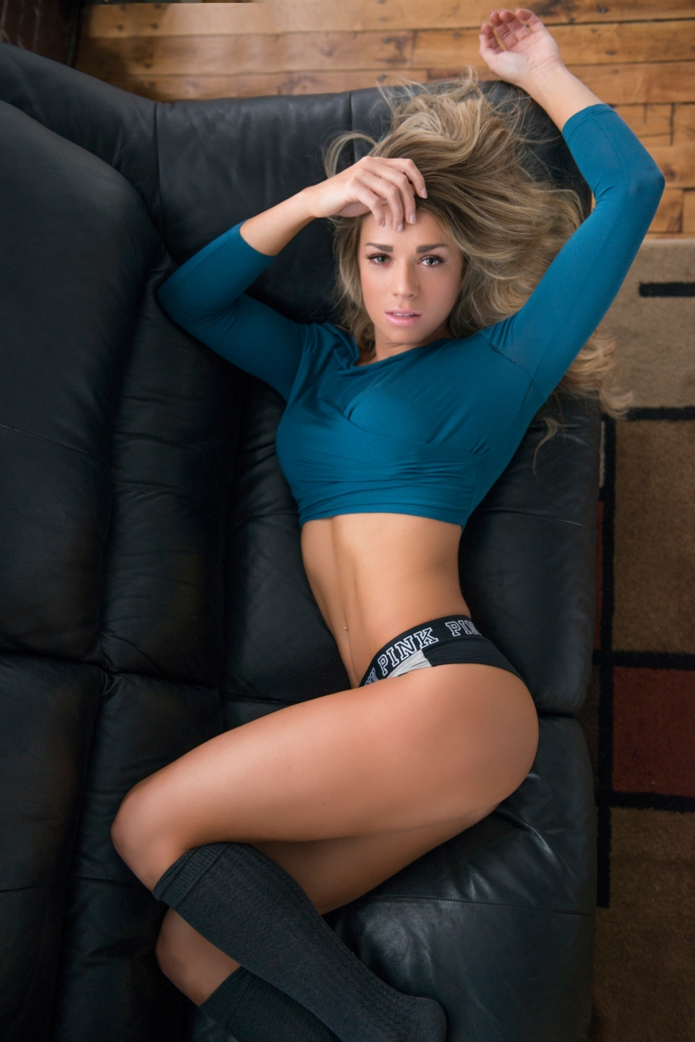 girl laying on black couch